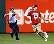 A Philadelphia policeman with taser in hand chases a Phillies' fan who ran on the field during the game with the Cardinals' during the 8th inning at Citizen's Bank Park.