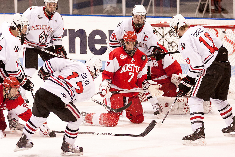 BU defenseman, Max Nicastro (7) blocks a shot from Northeastern forward, Steve Silva (17), during first period action at Matthews arena in Boston, Massachusetts.