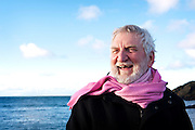 Older man laughing with sea behind him wearing pink scarf and black jacket in Portpatrick, Southern Upland Way