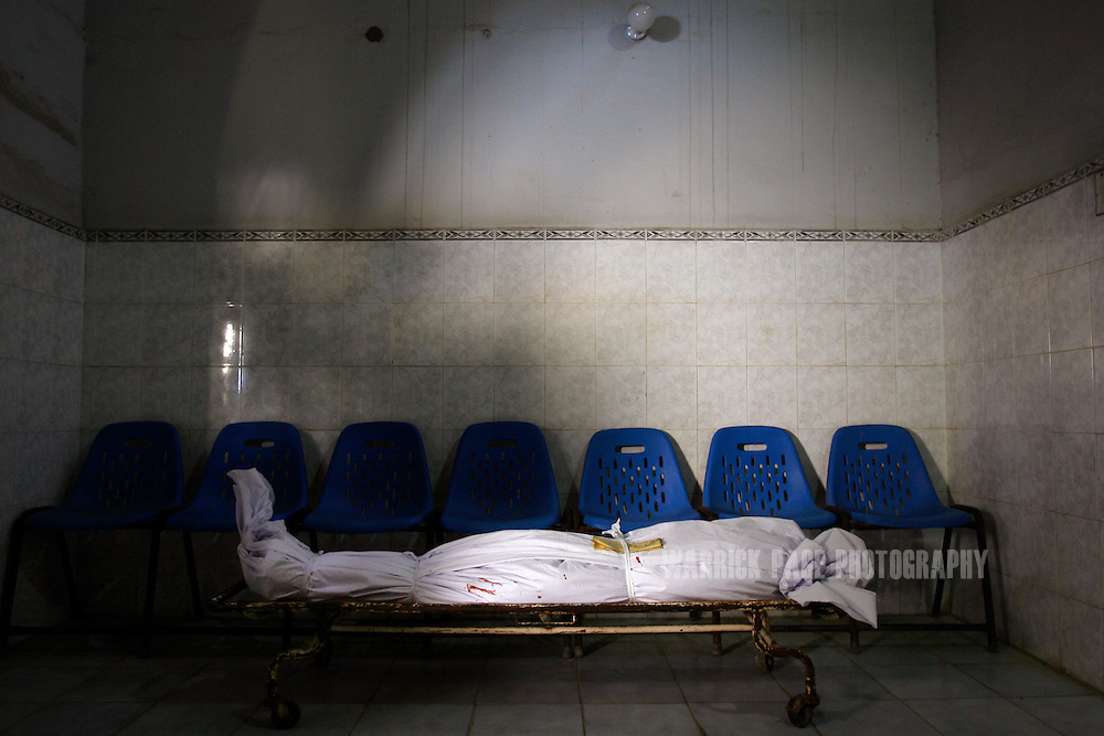 KARACHI, PAKISTAN - OCTOBER 19: A body lies wrapped in a shroud waiting to be collected by family at the Ehdi morgue, October 19, 2007, Karachi, Pakistan. At least 140 people were killed in a suicide bombing aimed at assassinating former prime minister and opposition leader, Benazir Bhutto. Bhutto was unharmed in the Karachi blast, only to be gunned down two months later by an unknown assassin at an election rally in the garrison city of Rawalpindi on December 27. Bhutto returned to Pakistan after 7 years in self-imposed exile on a US-brokered power-sharing deal with President Musharraf. The deal collapsed after Musharraf implemented emergency rule in November, arresting and imprisoning thousands of opposition members and lawyers. During her short-lived campaign, Bhutto had vowed to restore civilian leadership and democracy, and crush Islamic militancy throughout the country. (Photo by Warrick Page)