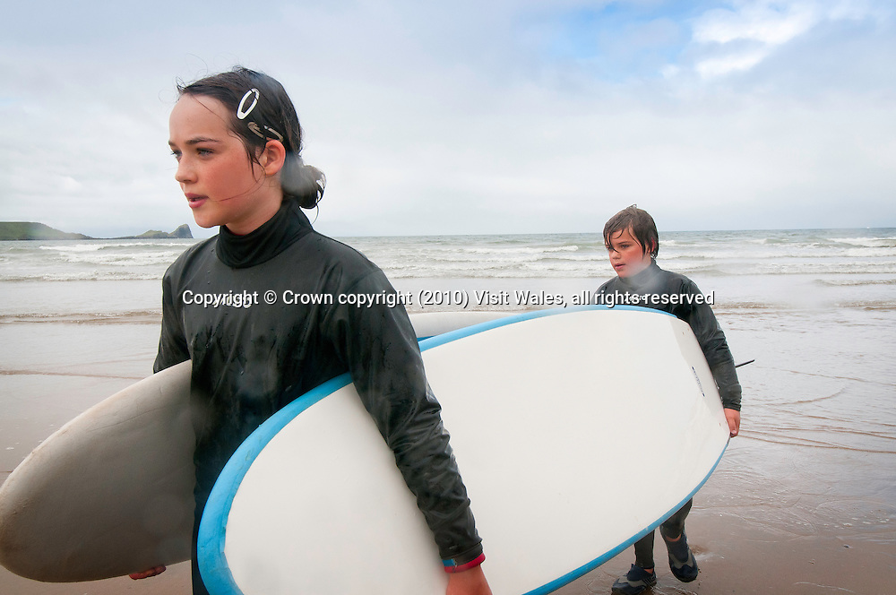 Boy and girl walking out of sea after surfing<br /> Rhossili<br /> Gower Peninsula<br /> Surfing<br /> Activities and Sports
