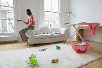 Woman sitting on edge of sofa watching television