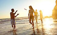 Friends play frisbee on El Matador Beach at sunset.