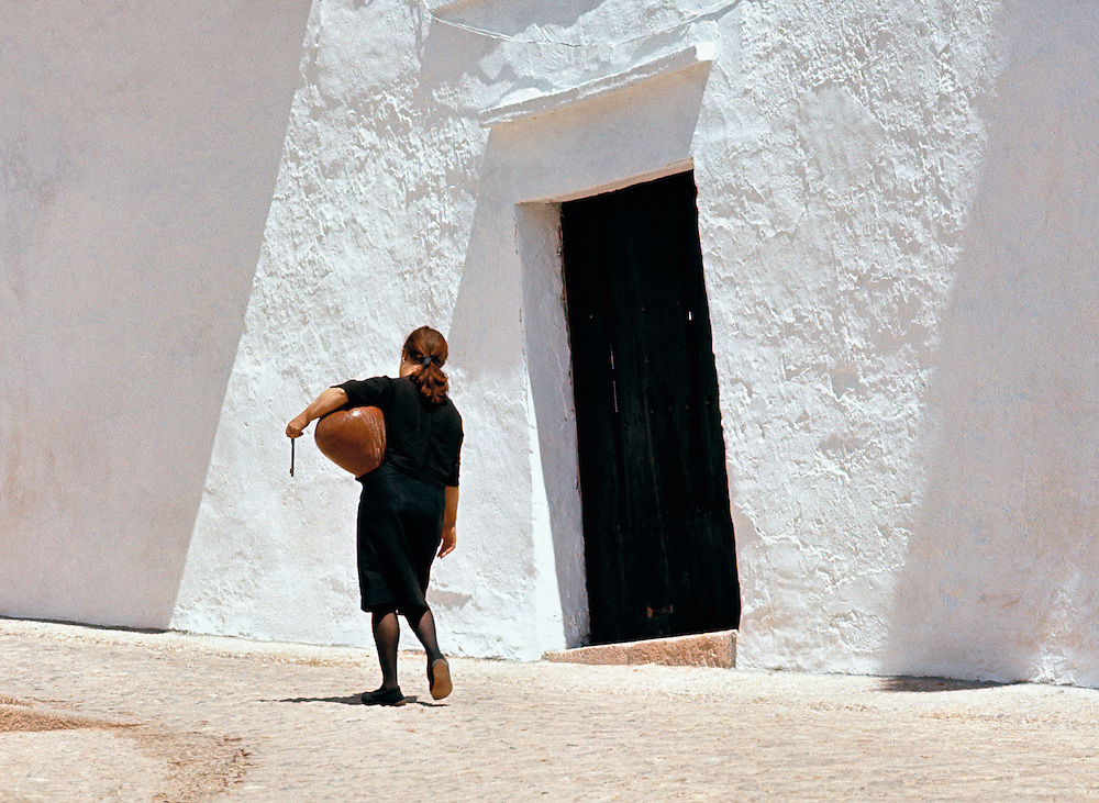 A woman carrying an earthenware water jug creates a striking contrast against the white-washed walls of Ronda, Spain.