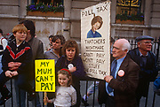 Before it erupts into a full-scale riot, families protest against Margaret Thatcher's Poll Tax policy, on 31st March 1990, in Trafalgar Square, London, England. Subsequently, angry crowds, demonstrating against Margaret Thatcher's local authority tax, stormed the Whitehall area and then London's West End, setting fire to a construction site and cars, looting stores up Charing Cross Road and St Martin's Lane. The anti-poll tax rally in central London erupted into the worst riots seen in the city for a century. Forty-five police officers were among the 113 people injured as well as 20 police horses. 340 people were arrested.