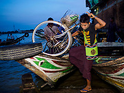 23 NOVEMBER 2017 - YANGON, MYANMAR: A passenger gets off a river taxi at the San Pya Fish Market jetty. San Pya Fish Market is one of the largest fish markets in Yangon. It's a 24 hour market, but busiest early in the morning. Most of the fish in the market is wild caught but aquaculture is expanding in Myanmar and more farmed fresh water fish is being sold now than in the past.    PHOTO BY JACK KURTZ