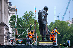 © Licensed to London News Pictures. 17/06/2020. London, UK. Metal sheets covering up former British Prime minister Winston Churchill's Statue in Parliament Square, London is taken down for President Macron's visit to England tomorrow. The statue was boarded up to protect it from large scale demonstrations last week. Photo credit: Alex Lentati/LNP