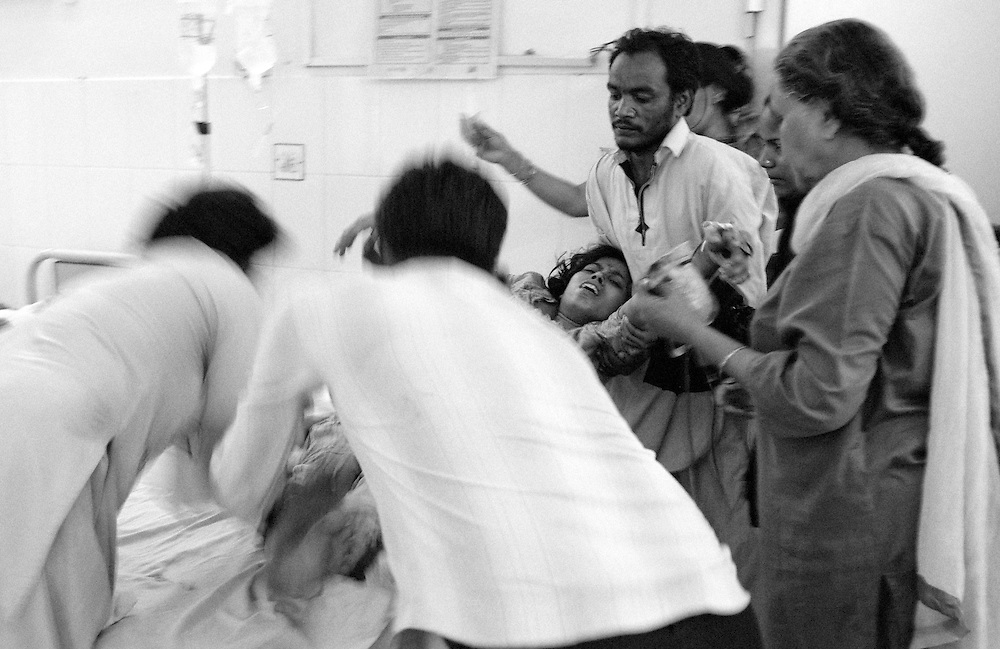 A young woman is being rushed to the operating theatre of the Qatar hospital after the doctors determined complications after she had an abortion. Qatar hospital, Orangi town, Karachi, Pakistan 2010
