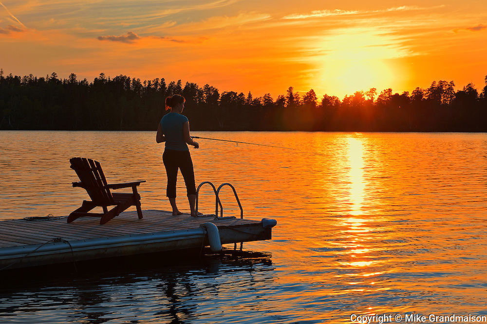 Woman fishing off the dock on Star Lake at sunset<br /> Whiteshell Provincial Park<br /> Manitoba<br /> Canada