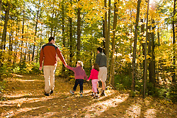 Two men and their young daughters walk on a woods road at the Clark Farm in Windham, Maine.