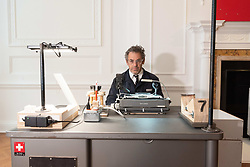 """October 5, 2018 - London, London, UK - London, UK. American artist Tom Sachs producing a passport with his 24hliveperformanceSwiss Passport Office. The 24hliveperformanceSwiss Passport Office is on show at the Galerie Thaddaeus Ropac. Those wishing to purchase a passport will be photographed and have their name hand-typed onto a serial-numbered passport issue, stamped with a Studio endorsement and entered into the permanent database. Passports cost €20 (no British pounds will be accepted). Swiss Passport Officeencompasses contemporary concerns relatingto Brexit, Syria and Trump's immigration policies and their challenge to the notion of global citizenship. """"To effect change, we must first imagine the world not the way it is, but the way we want it to be,"""" Sachs says. (Credit Image: © Ray Tang/London News Pictures via ZUMA Wire)"""