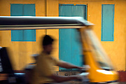 Rickshaw driver passing a yellow house in Cochin, India.