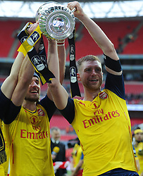 Arsenal's Aaron Ramsey and Per Mertesacker celebrate with the FA Cup - Photo mandatory by-line: Dougie Allward/JMP - Mobile: 07966 386802 - 30/05/2015 - SPORT - Football - London - Wembley Stadium - Arsenal v Aston Villa - FA Cup Final