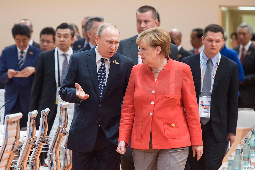 07 JUL 2017, HAMBURG/GERMANY:<br /> Vladimir Putin, Praesident Russische Foerderation, und Angela Merkel (R), CDU, Bundeskanzlerin, auf dem Weg durch den Sitzungssaal, 1. Arbeitssitzung, G20 Gipfel, Messe<br /> IMAGE: 20170707-01-011<br /> KEYWORDS: G20 Summit, Deutschland