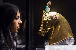 "© Licensed to London News Pictures. 25/10/2019. LONDON, UK. A staff member views one of two gold and gem set horse head sculptures, 'Lakshmi' and 'Indra', 1949, by Herbert Haseltine (Est: GBP600 - 800k).  Preview of ""GOLD: The Midas Touch"" at Sotheby's in New Bond Street.  Artworks spanning six centuries dedicated to gold will be offered for sale on 29 October.  Photo credit: Stephen Chung/LNP"