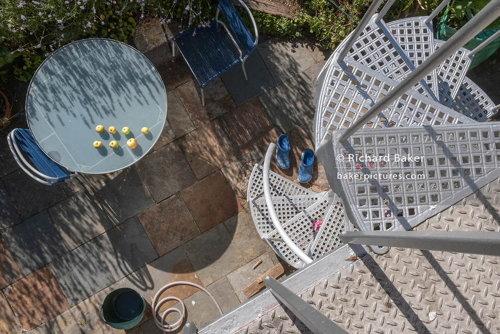 Beneath a silver-painted spiral staircase, home-grown apples ripen In sunshine on a garden table, on 29th July 2020, in London, England.