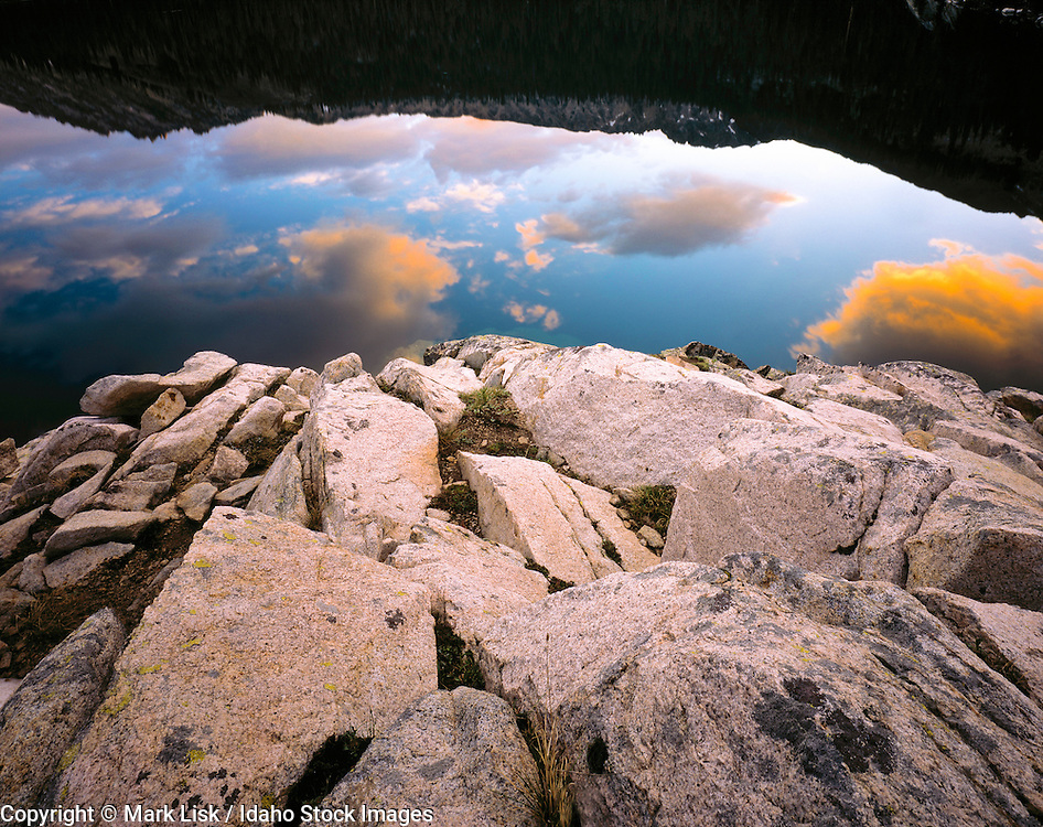 Bordered by slabs of granite, Cramer Lake reflects the passing clouds in its crystal waters. Sawtooth Wilderness Area, Idaho.