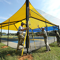 Chris Hughes, Carl Scherff and Vonjacques Hall, employees with Ivey Fence in Tupelo, install new fencing around the Basketball courts at Gumtree Park in Tupelo on Monday.
