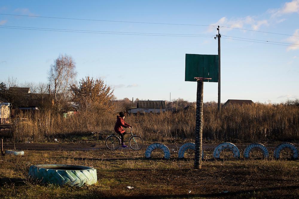Une femme &agrave; v&eacute;lo devant une aire de jeux, dans l'un des quartiers r&eacute;sidentiels de la ville, 8 decembre 2015.<br /> <br /> A woman rides a bicycle past a playground on December 8, 2015 on the outskirts Hlukhiv, Ukraine.