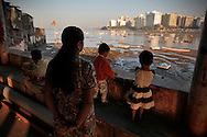 A mother and her three children wait for her husband to arrive from a morning fishing trip.  The small fishing village of Machimaar Nagar struggles to hold on as the explosive growth of Mumbai begins to encroach on its space.