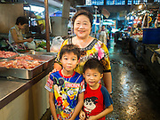 20 APRIL 2015 - BANGKOK, THAILAND:   A family shopping in the Talat Phlu market in the Thonburi section of Bangkok. The boys were wearing tee shirts with popular US cartoon characters (in this case Mickey Mouse) and Japanese Anime.   PHOTO BY JACK KURTZ