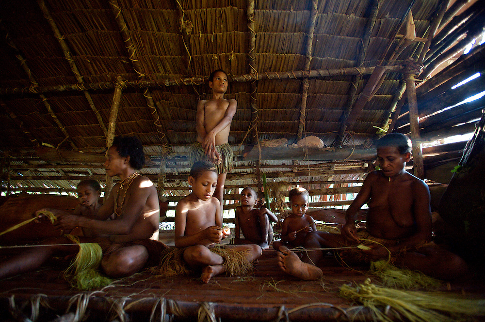 Here the women and young girls are making grass skirts from the sago plalm leaves.West Papua is home to over 300 tribes. They have inhabited the island for more than 40,000 years. Many of the last remaining tribal cultures on our planet can be found in West Papua. An astounding 15% of the world's languages are spoken there, by just 0.01% of the global population.