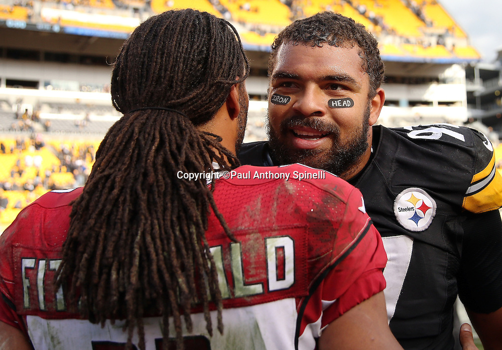 "Pittsburgh Steelers defensive end Cameron Heyward (97) is congratulated on the win by Arizona Cardinals wide receiver Larry Fitzgerald (11) after the game while wearing eye black tape marked with ""Iron Head"" in tribute to his father (former New Orleans Saints running back Craig ""Ironhead"" Hayward who died of brain cancer) during a breast cancer awareness game at the 2015 NFL week 6 regular season football game against the Arizona Cardinals on Sunday, Oct. 18, 2015 in Pittsburgh. The Steelers won the game 25-13. (©Paul Anthony Spinelli)"