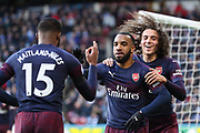Arsenal forward Alexandre Lacazette (9) celebrates with team mates Arsenal midfielder Matteo Guendouzi (29) and Arsenal midfielder Ainsley Maitland-Niles (15) after scoring his team's second goal during the Premier League match between Huddersfield Town and Arsenal at the John Smiths Stadium, Huddersfield, England on 9 February 2019.