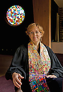 Portrait of a Unitarian Universalist woman minister in her robe and colorful stole, seated beneath the multicolored rose window of her church