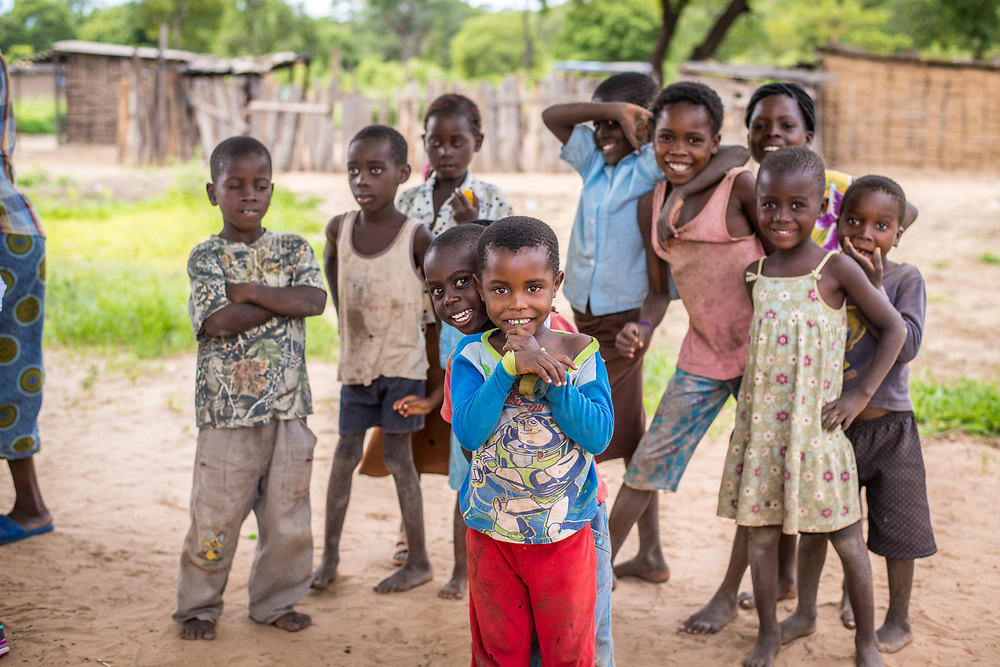 A group of young Zambian children pose and gather together to smile for a photo Livingstone, Zambia