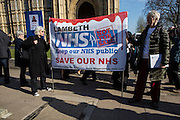 Two women stand holding a banner campaigning to prevent Lambeth NHS Trust from being sold and privatized.  Another woman holds a placard against Virgin Health who are trying to buy the health service. They are demonstrating outside the Houses of Parliament in London, United Kingdom,