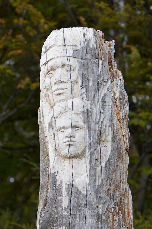 A totem pole carved out of a tree stump stands in a forested area near the Perito Moreno Glacier. The glacier is a popular hiking destination in Los Glaciares National Park, Argentina.