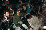 Winter Carnival, Quebec.Saturday night parade watchers, including a drunken man with a penis-shaped nose warmer. Canada.