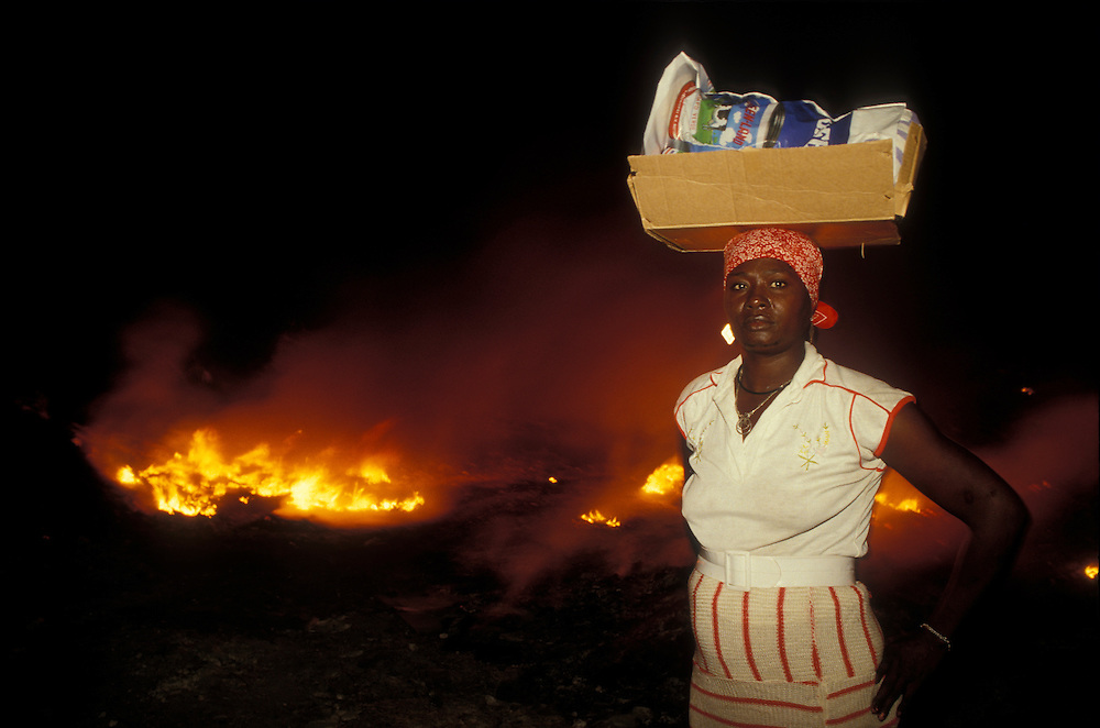 Haiti, Port-au-Prince, Market woman carries goods on her head past garbage fire at night