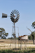 Windmill and rusted water tank in farm paddock in rural country Alectown, New South Wales, Australia. <br />