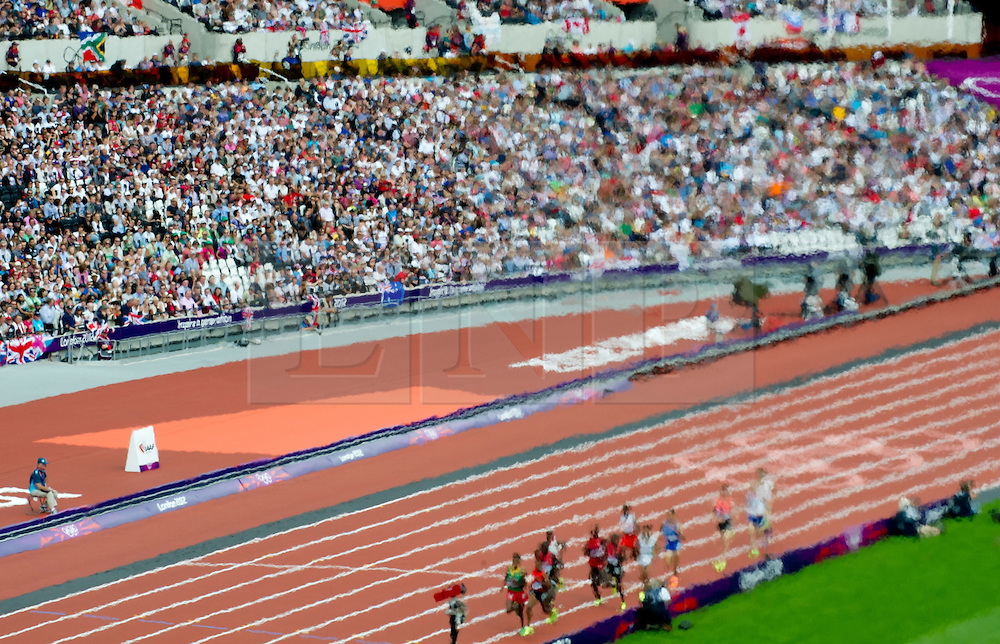 © Licensed to London News Pictures. 08/08/2012. London,UK.Athletes, seen through the gaze of the Olympic flame, run in the Men's 5000m Round 1, during the London 2012 Olympic Games .  Photo credit : Bogdan Maran/LNP/BPA