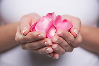 Woman cupping hands full of petals mid section close-up