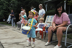Patriotic youngsters await arrival of parade bands.