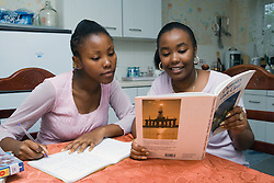 Sisters sitting at kitchen table studying for school exams,