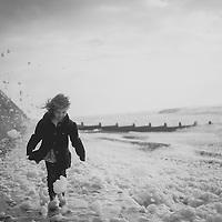 Young girl walking beside the sea
