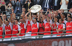 Per Mertesacker ( left centre ) and Mikel Arteta of Arsenal lift the Community Shield after their team win the match - Mandatory byline: Paul Terry/JMP - 07966386802 - 02/08/2015 - Football - Wembley Stadium -London,England - Arsenal v Chelsea - FA Community Shield