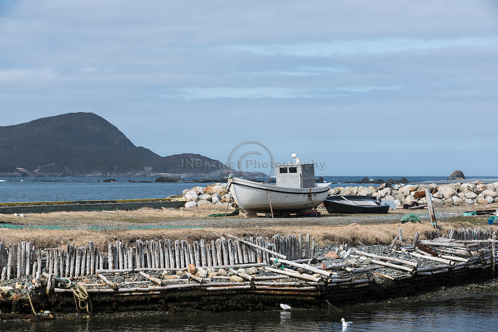 Boats on land and rustic dock sheltered from the Atlantic ocean.  Ferryland, NL Canada
