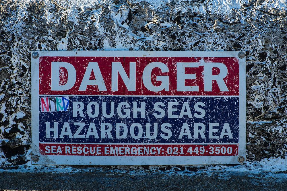 Danger sign warning of rough seas, Kalk Bay harbour, False Bay, Western Cape, South Africa