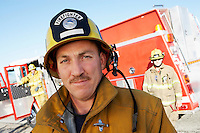 Fire fighter standing in front of colleagues and fire engine