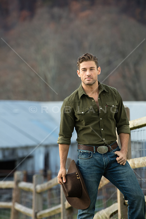 handsome cowboy holding his hat on a ranch