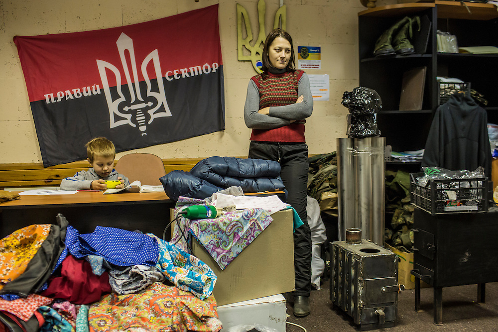 DNIPROPETROVSK, UKRAINE - NOVEMBER 16, 2014:  Yana Sobolenko, 39, an engineer, and her son Roman at the Dnipropetrovsk Volunteer Logistics Center, a charity organization that produces supplies for pro-Ukrainian fighters battling rebels in the country's East, in Dnipropetrovsk, Ukraine. CREDIT: Brendan Hoffman for The New York Times