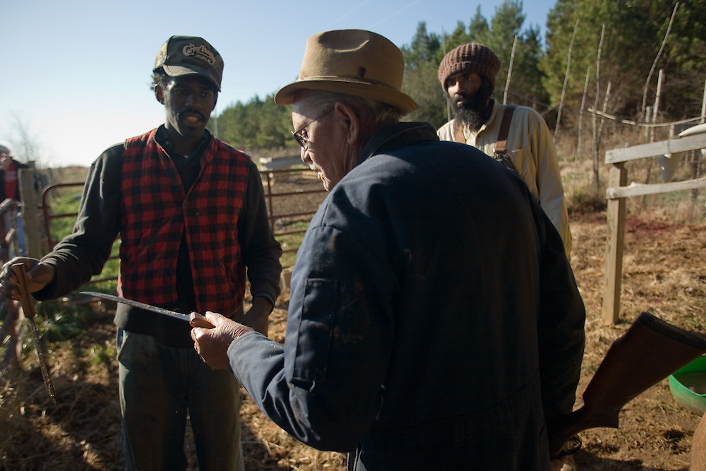 Young farmers Justin Robinson, left, and Tahz Walker, right, listen to Elwood Whitmore explain the proper way to stick a hog to ensure that it dies quickly. Robinson and Walker sought out the elder Whitmore for help with butchering their hogs after learning that he was the authority in the Piedmont area. ?He knew everything to do and what not to do, literally, down to the inch,? said Robinson.