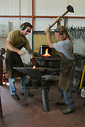 Old style hand made iron workers in a small work shop, force shaping a red hot iron rod