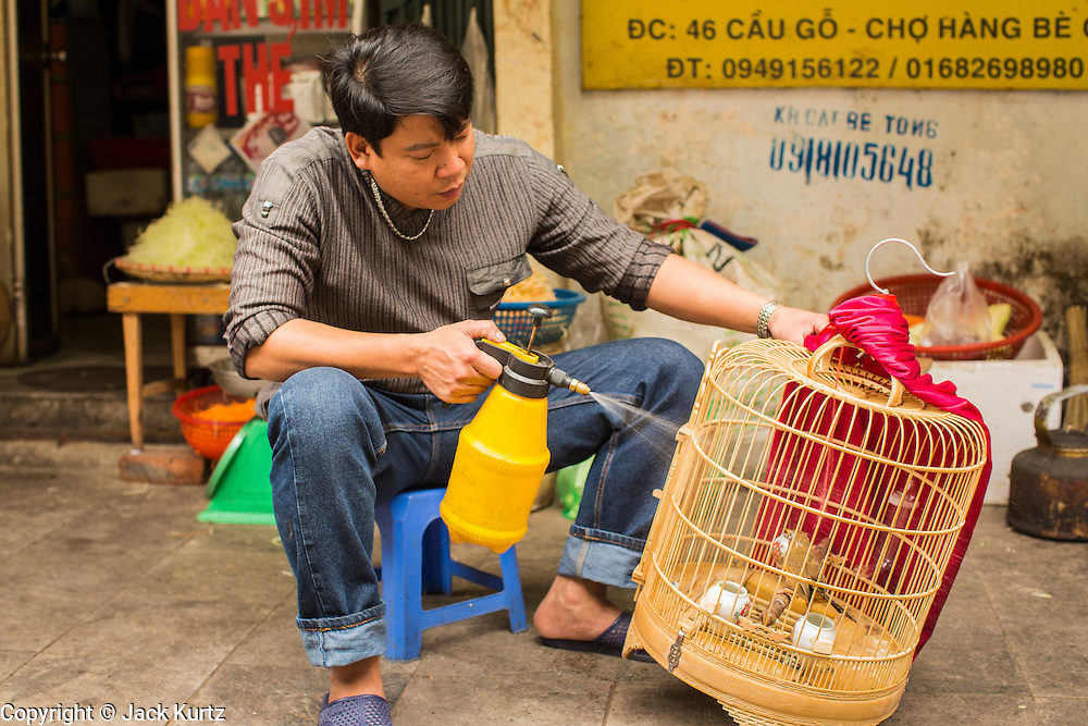01 APRIL 2012 - HANOI, VIETNAM:  A man waters his bird on a street in Hanoi, the capital of Vietnam. Many people in the north of Vietnam keep songbirds in ornate cages in front of their homes and shops.     PHOTO BY JACK KURTZ
