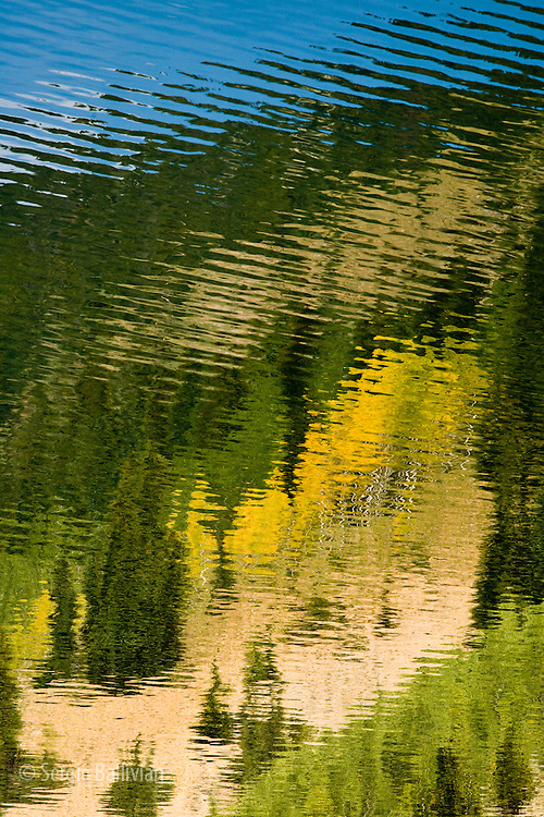 Abstract images of Fall landscape colors are reflected in a Colorado lake.